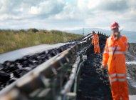 Travailleurs du charbon inspection de bande transporteuse — Photo de stock