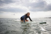 Senior woman on surfboard in sea, paddleboarding — Stock Photo