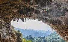 Scalatore femminile arrampicata Dan di Odino - una scogliera di calcare a Yangshuo, Guangxi Zhuang, Cina — Foto stock