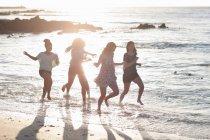 Mulheres correndo juntas na praia — Fotografia de Stock