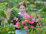 A young girl with flowering pot plants — Stock Photo