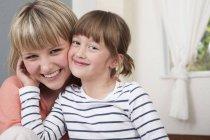 Портрет молодой женщины и девочки-подростка, улыбающейся и смотрящей в камеру — стоковое фото