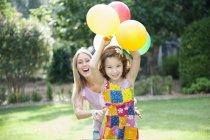 Mutter und Tochter spielen im Garten mit Luftballons — Stockfoto