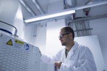 Assistant de laboratoire travaillant sur des équipements scientifiques — Photo de stock