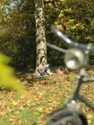 Woman with picnic under tree in Autumn — Stock Photo