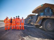 Group portrait of dumper truck drivers standing in opencast coalmine — Stock Photo