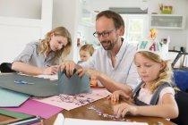 Familia con dos hijas haciendo coronas de papel - foto de stock