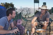 Двоє молодих чоловіків кемпери чаті і готувати їжу — стокове фото