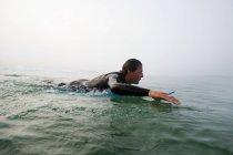 Mann auf Surfbrett im Ozeanwasser liegend — Stockfoto