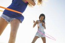 Two young Women using hula hoop on beach — Stock Photo