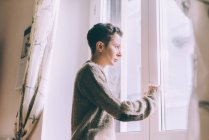 Portrait of young woman staring through window at home — Stock Photo