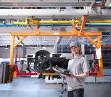 Female Worker With Car Parts In Plant — Stock Photo