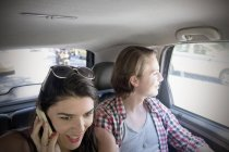 Young couple in car, woman on cell phone — Stock Photo