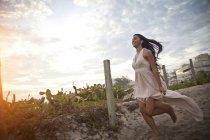 Mujer adulta corriendo a lo largo de pasarela arenosa hacia la playa - foto de stock