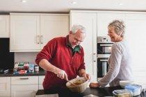 Senior couple baking together in kitchen — Stock Photo
