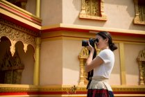 Woman taking photograph outside building, Luang Prabang, Laos — Stock Photo