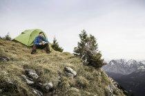 Молоді чоловіки мандрівного пити каву перед намет на Klammspitze горі, Баварія, Німеччина — стокове фото