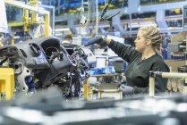Женщина-ученица инженера на производственной линии на автомобильном заводе — стоковое фото