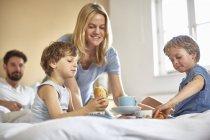 Jungen frühstücken im Bett der Eltern — Stockfoto