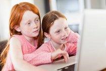 Chicas usando el ordenador portátil juntos - foto de stock