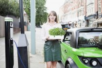 Woman carrying flowerbox on city street — Stock Photo