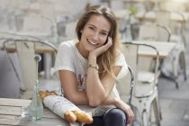Giovane donna seduta al caffè pavimentazione con baguette, mano sul mento guardando la fotocamera sorridente — Foto stock