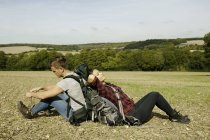 Young hiking couple sitting back to back in field, Great Missenden, Buckinghamshire, U.K — Stock Photo