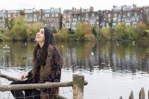 Giovane donna rilassante in riva al lago, Hampstead Heath, Londra — Foto stock
