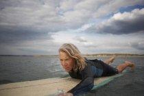Пожилая женщина на доске для серфинга в море, паддлбординг — стоковое фото