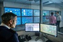 Tutor em monitores do computador que prestam atenção a estudantes no simulador do quarto de motor do navio — Fotografia de Stock