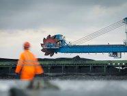 Trabajador portuario con maquinaria pesada - foto de stock