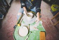 Erhöhte Ansicht der Mitte erwachsenen Mann, der Tontopf auf der Töpferscheibe — Stockfoto