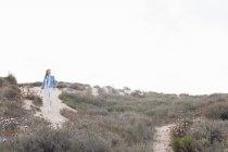Самотній середині дорослої жінки прогулюються в прибережних піщані дюни, Сардинія, Італія — стокове фото