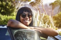 Portrait of young woman standing beside car, leaning on open car door — Stock Photo