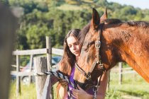 Woman tethering horse to fence post — Stock Photo