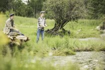 Brother and sister on riverbank fishing — Stock Photo