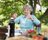 Старша жінка, яка виступає салат на відкритому столі в саду — стокове фото