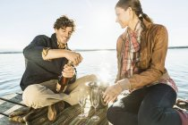 Couple sitting by lake with wine — Stock Photo