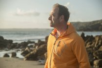 Mature man, standing on beach, looking out to sea — Stock Photo