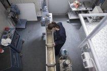 Высокоугол обзора женщин-инженеров, проверяющих производственные машины — стоковое фото