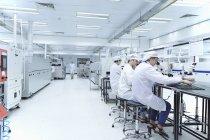 Рабочие мужчины и женщины используют микроскопы на высокотехнологичной фабрике — стоковое фото