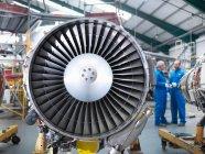 Реактивные двигатели самолета с авиаинженерами на заднем плане — стоковое фото