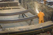 Vista posteriore della costruzione di metallo di macinazione del lavoratore nella fabbrica di fabbricazione marina — Foto stock