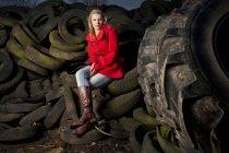 Девушка сидит на брошенные шины — стоковое фото