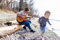 Father and son with guitars by creek — Stock Photo