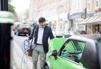 Uomo ricarica auto elettrica sulla strada — Foto stock