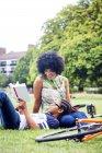 Мальчик и мать отдыха и чтения в парке — стоковое фото