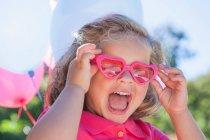 Девушка в розовых очках в форме сердца — стоковое фото
