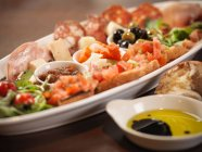 Plate of antipasto on table with olive oil in restaurant — Stock Photo