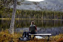 Hiker resting on bench, looking out at lake, Kesankijarvi, Lapland, Finland — Stock Photo